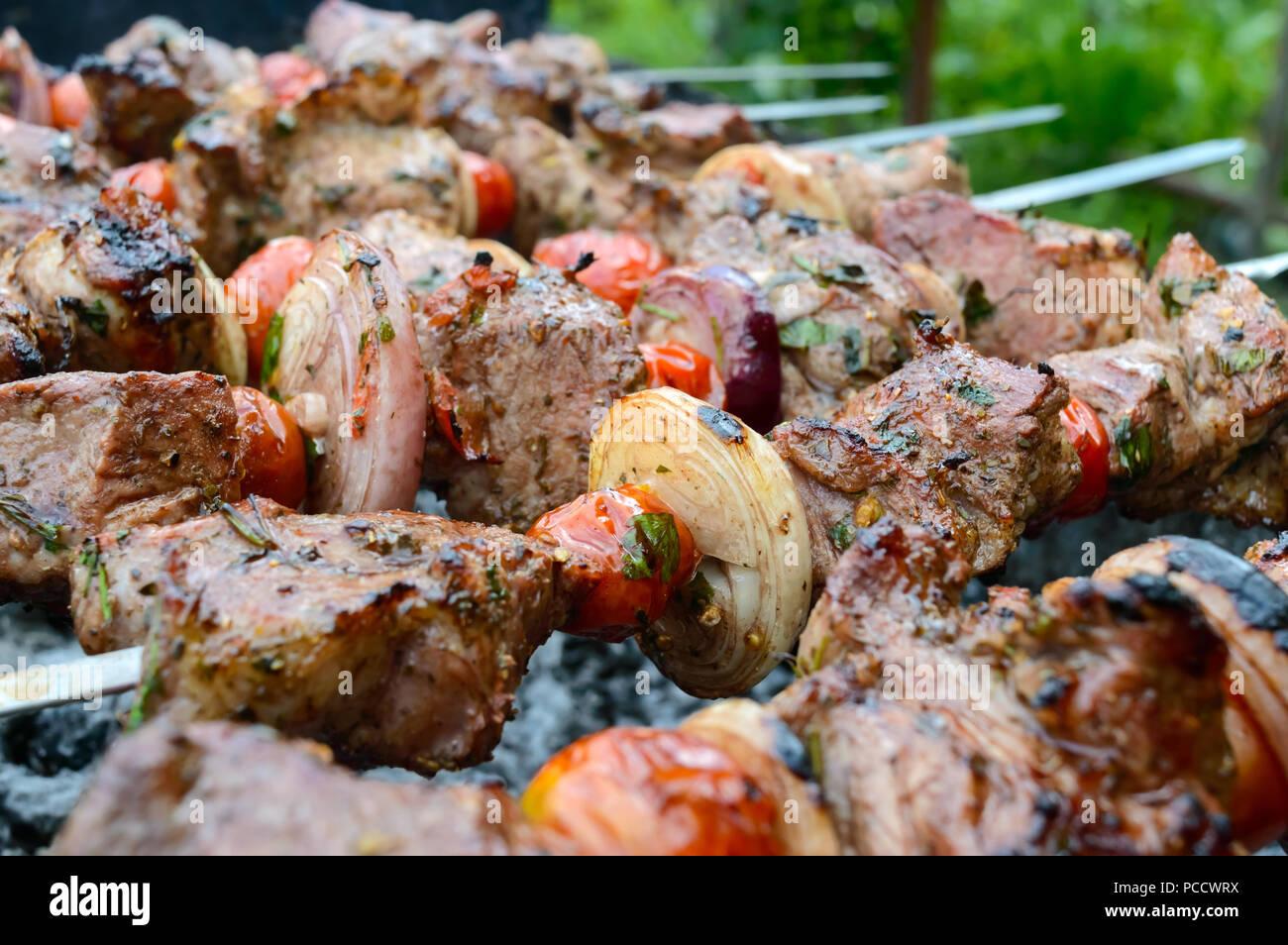 Succosa shish kebab di carne di maiale, pomodori su spiedini fritti su un fuoco all'aperto su uno sfondo di natura. Barbecue. Close-up Immagini Stock