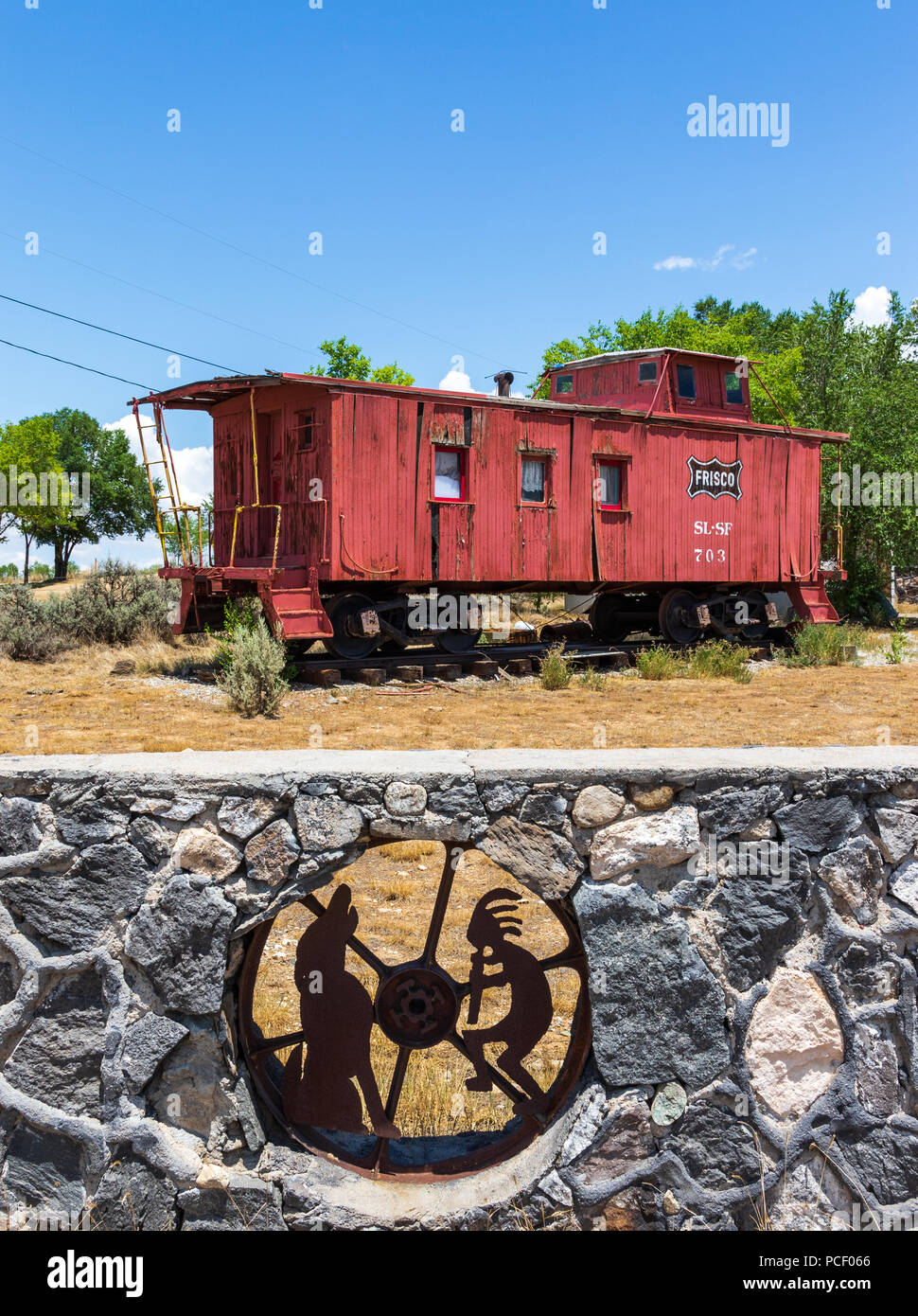 TAOS, NM, Stati Uniti d'America-12 luglio 18: una parete di roccia con metallo iconica figure di Kokopelli e Coyote incastrata dentro di essa, con un treno caboose al di là. Immagini Stock