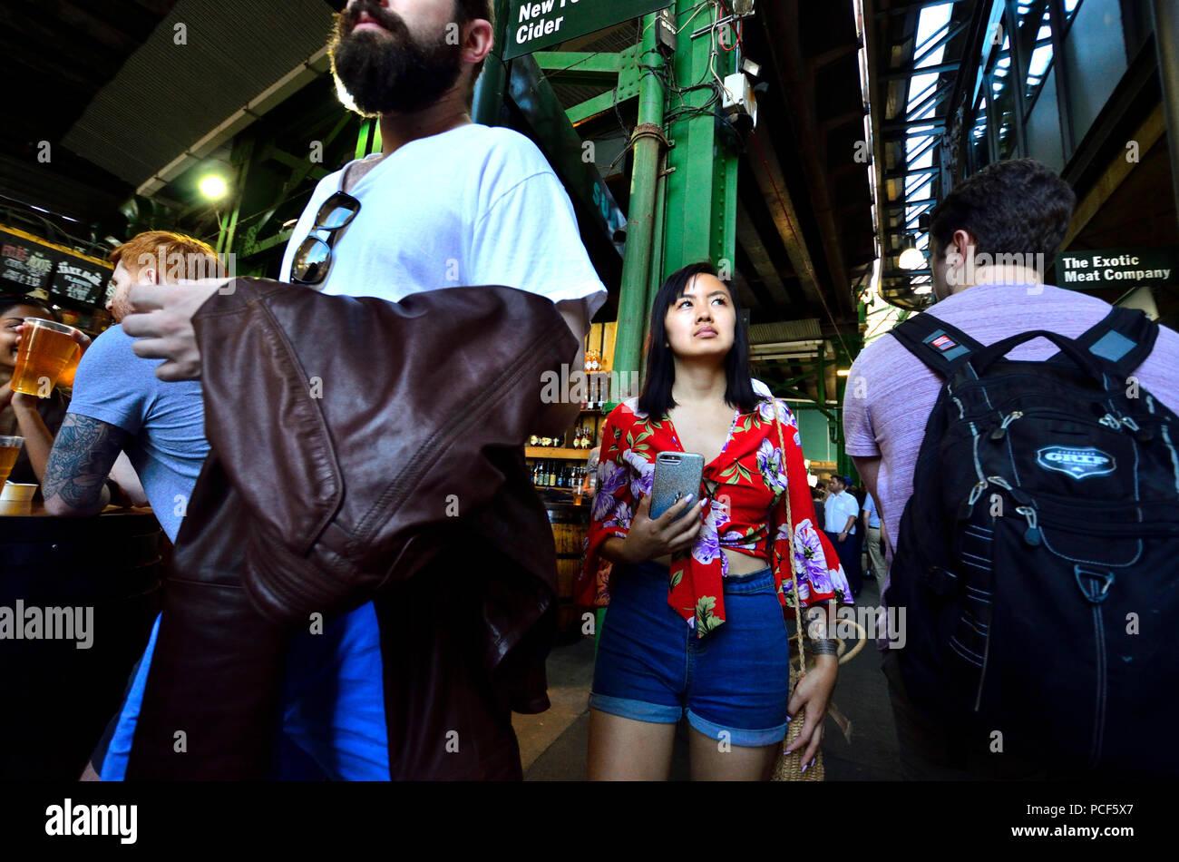 Turisti asiatici in un affollato mercato di Borough, Southwark, Londra, Inghilterra, Regno Unito. Foto Stock