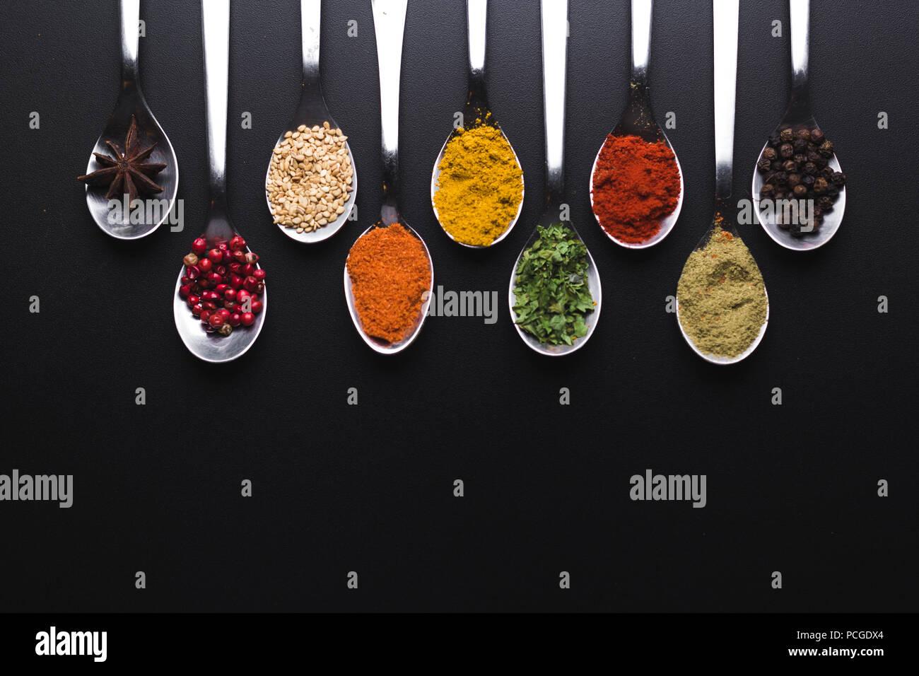 Spezie e condimenti per la cottura su uno sfondo nero, l'immagine ha uno spazio disponibile per aggiungere testi Immagini Stock