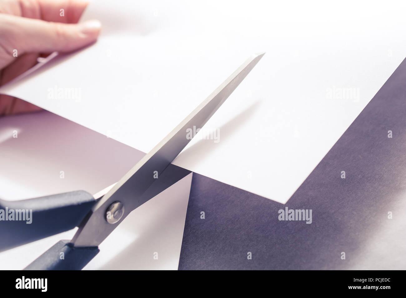 Un paio di forbici da taglio carta bianca, sostenuto da mani femminili Immagini Stock