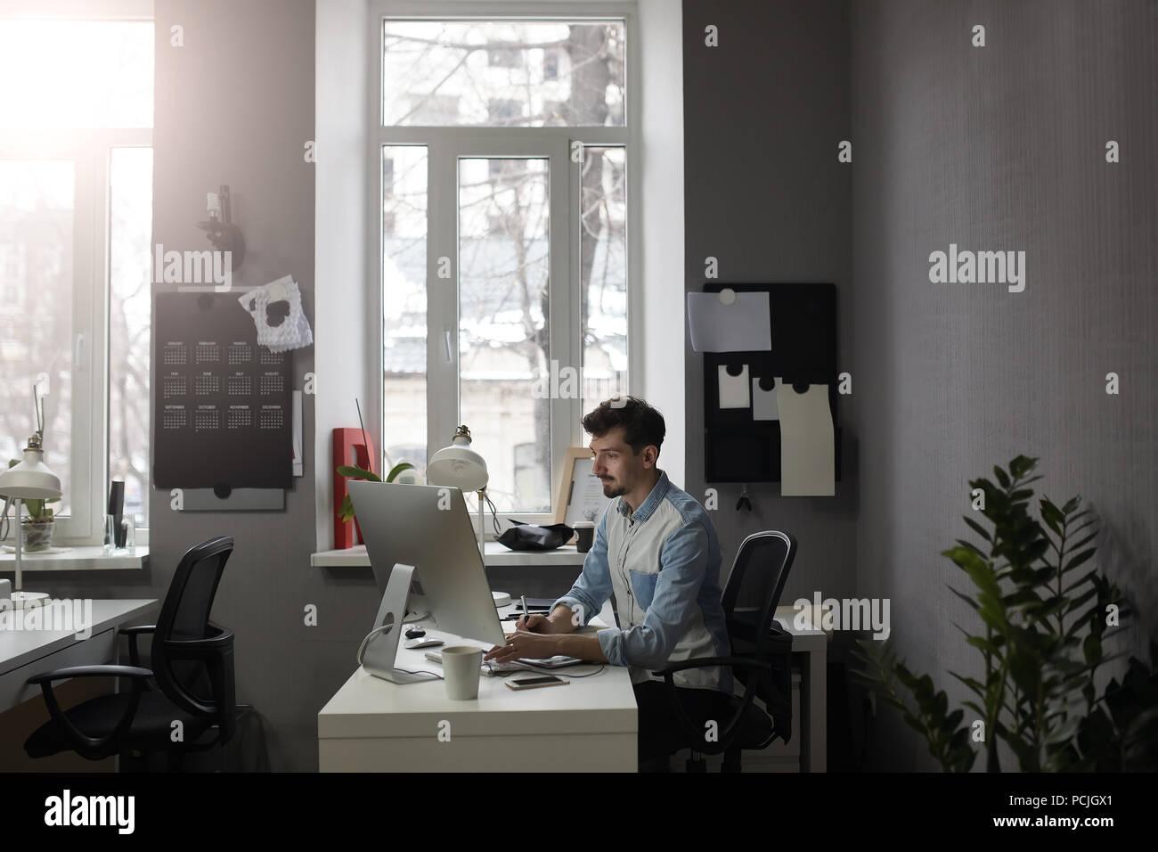 Giovani intelligenti barbuto uomo che lavora presso i moderni loft studio-offi Immagini Stock