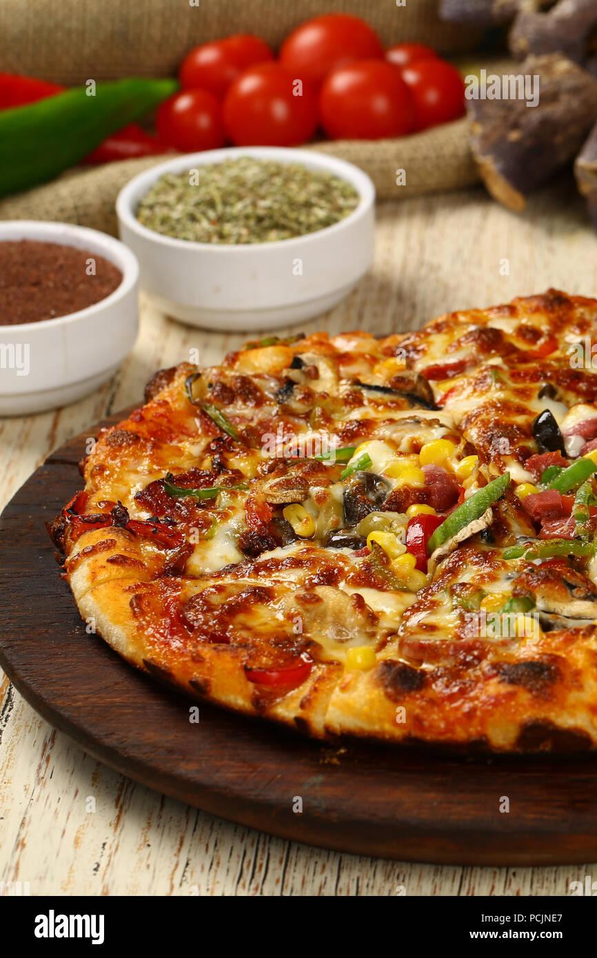 Una deliziosa pizza italiana sulla tavola di legno Immagini Stock