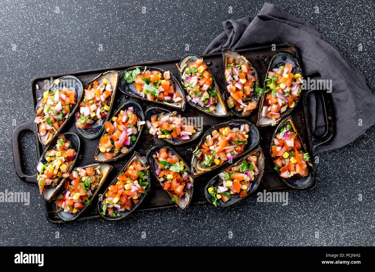 La cucina peruviana. Choros a la chalaca. Grande cozze, choros zapatos condito con viola, cipolla, pomodoro, mais e limone. Vista superiore, sfondo nero. Tradizionale piatto peruviano Immagini Stock