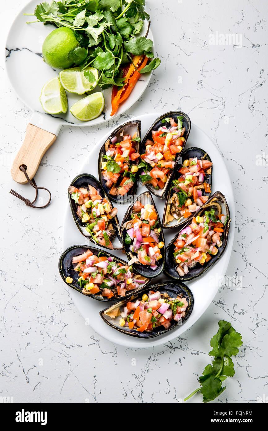La cucina peruviana. Choros a la chalaca. Grande cozze, choros zapatos condito con viola, cipolla, pomodoro, mais e limone. Vista superiore, sfondo bianco. Tradizionale piatto peruviano Immagini Stock