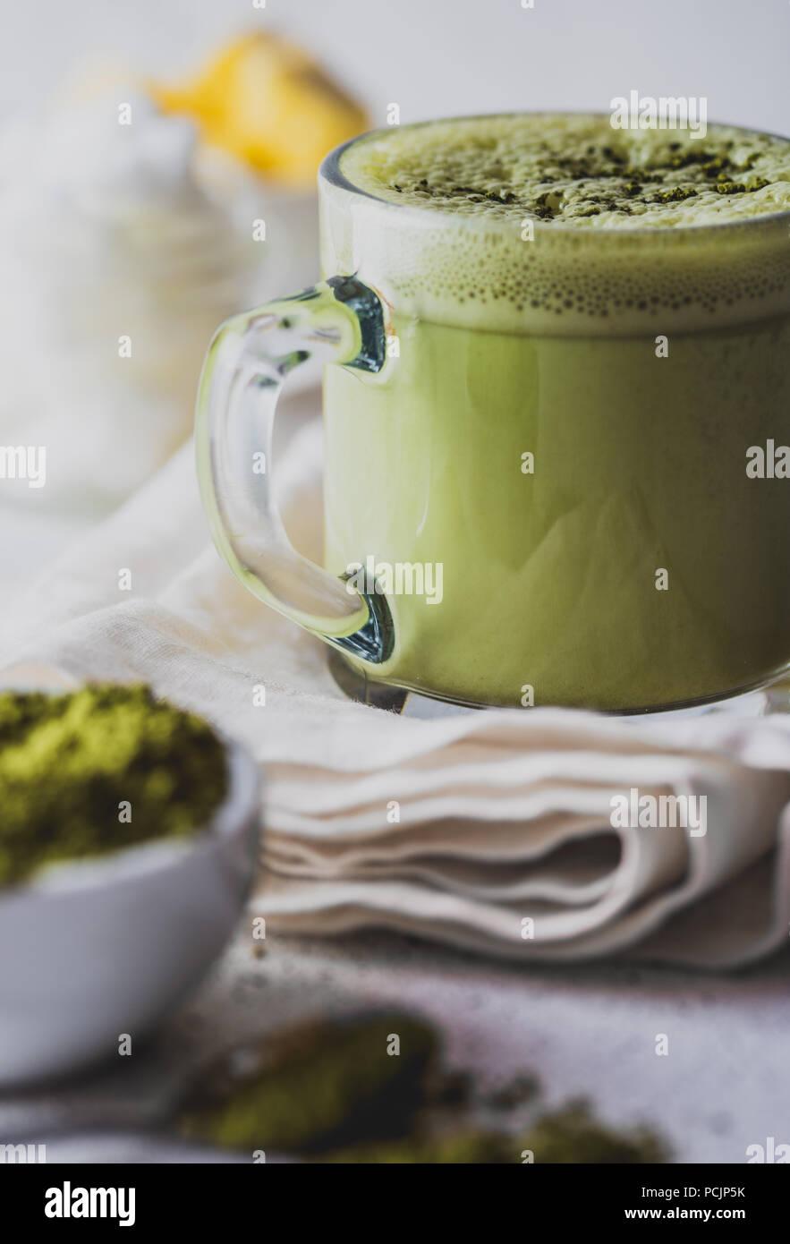 BULLETPROOF MATCHA. Ketogenic dieta cheto bevanda calda. Il tè matcha miscelato con olio di noce di cocco e il burro. Tazza di bulletproof matcha e ingredienti su sfondo bianco Immagini Stock