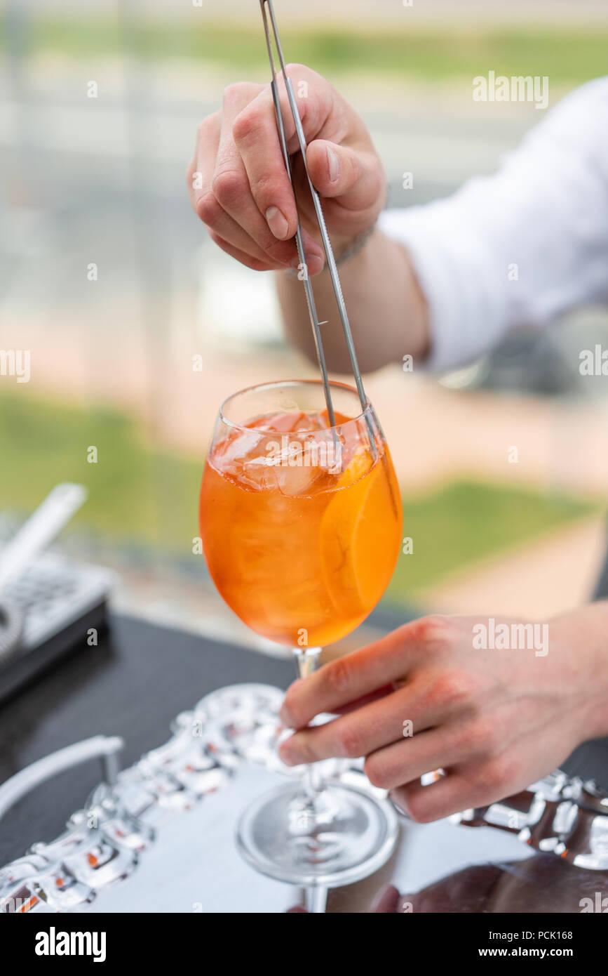 Barista rende cocktail Aperol spritz. Colmi di vetro, il fuoco selettivo. Bevanda alcolica basata sul banco bar con cubetti di ghiaccio e arance. parte esterna Immagini Stock