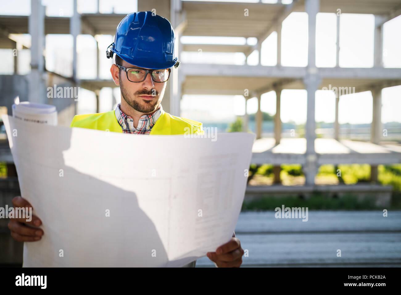 Tecnico delle Costruzioni in hardhat con progetto a mani Immagini Stock