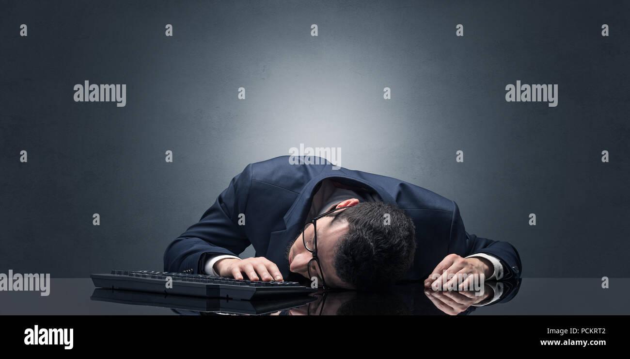 Giovane imprenditore si è addormentato al suo posto di lavoro con spazio di copia Foto Stock