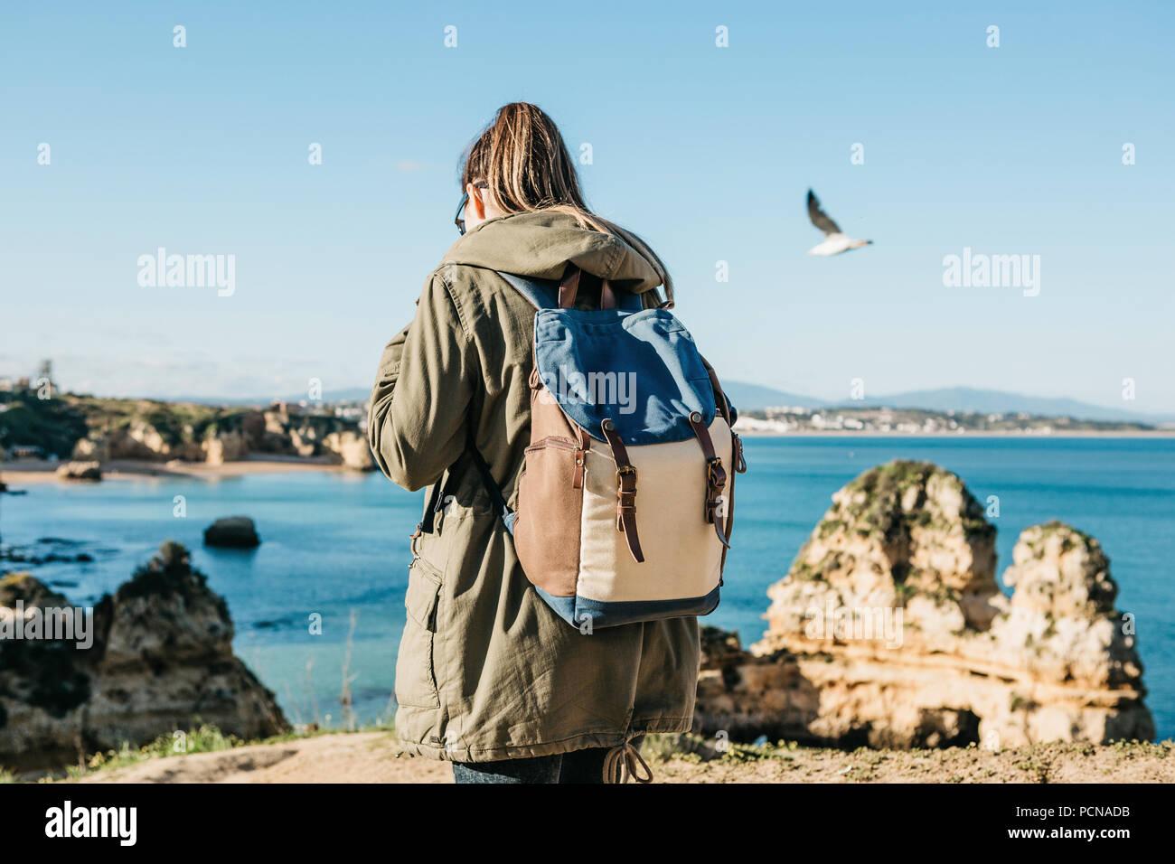 Un turista o viaggiatore con uno zaino passeggiate lungo la costa dell'Oceano Atlantico e si ammira la splendida vista dell'oceano vicino la città chiamata Lagos in Portogallo. Immagini Stock