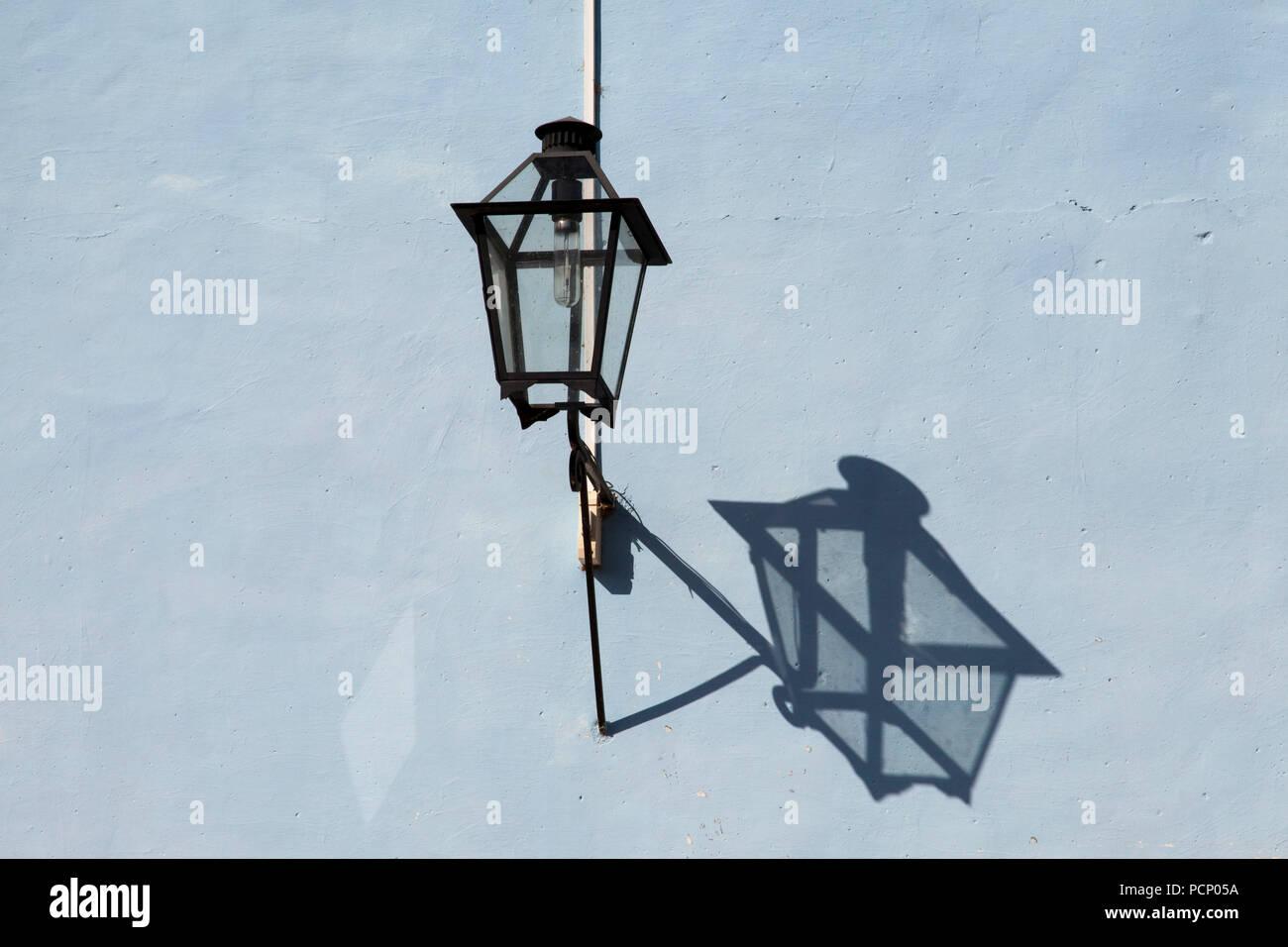Caraibi, Cuba, Trinidad, nero ombra proiettata da un lampione sulla parete esterna Foto Stock
