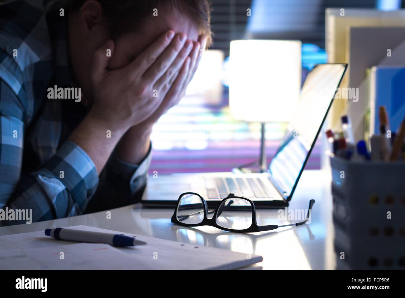 Problemi sul lavoro. Triste, infelice e stanco uomo che ricopre la faccia con le mani in ufficio o a casa durante la notte. Burnout, lo stress e il mobbing sul posto di lavoro o di depressione. Immagini Stock