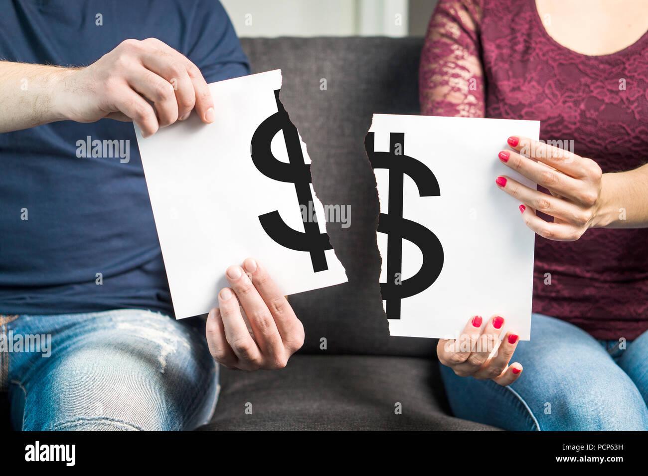 La lotta contro il denaro o di argomento finanziario concetto. L uomo e la donna holding di carta strappata con il simbolo del dollaro. Immagini Stock