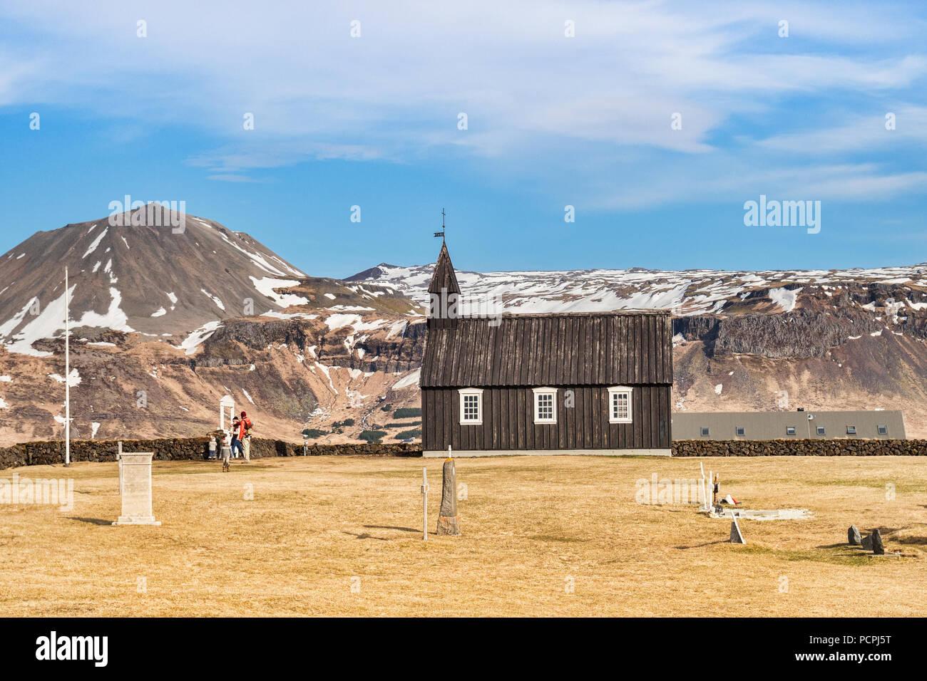 16 Aprile 2018: Budir, Snaefellsnes Peninsula, West Islanda - La piccola chiesa nera e una famiglia di turisti in visita. Immagini Stock
