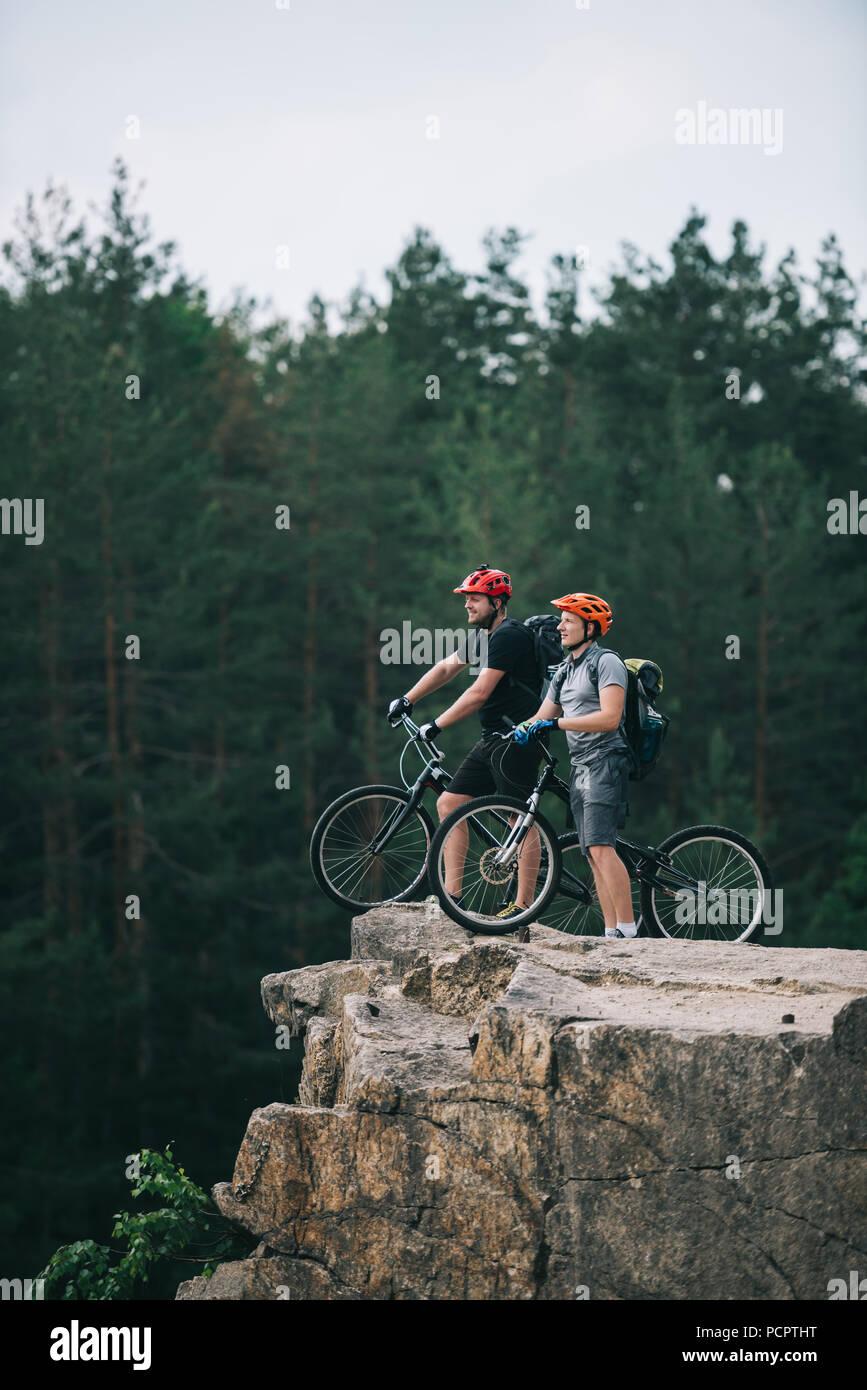 Vista laterale di felice giovani motociclisti di prova permanente sulla scogliera rocciosa con sfocato pineta sullo sfondo e guardando lontano Immagini Stock