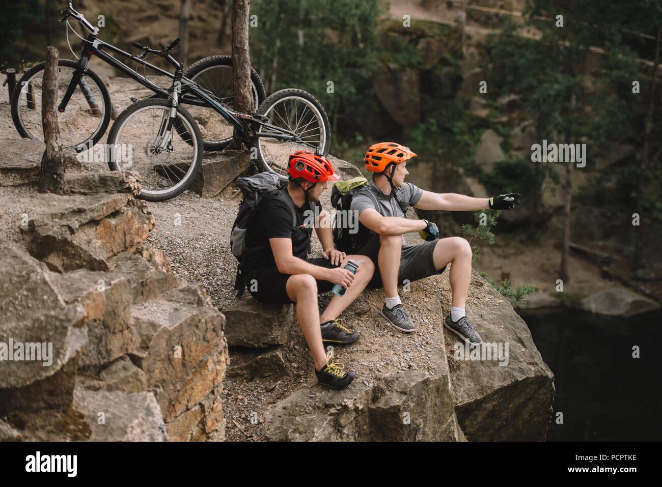 Angolo di alta vista di giovani motociclisti prova rilassante sulla scogliera rocciosa dopo ride e guardando lontano Immagini Stock