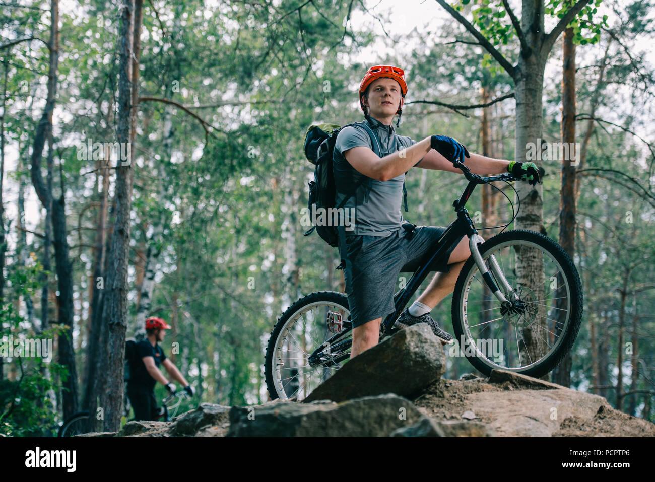 Prova di giovani biker permanente sulla roccia alla bella foresta e guardando lontano con il suo amico sfocati sullo sfondo Immagini Stock
