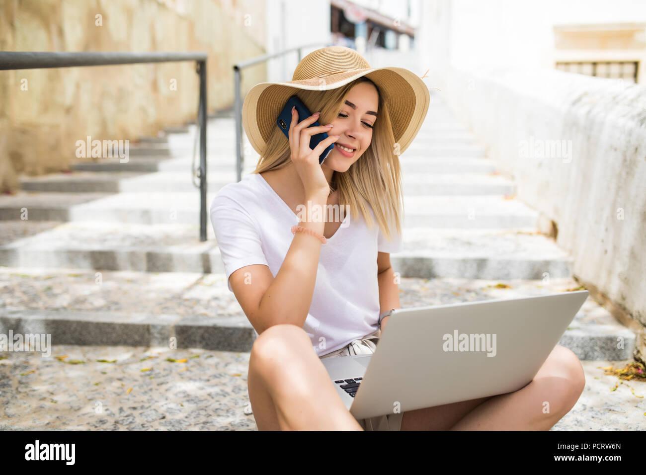 be6523e0b147 Bella donna che indossa casual vestito estivo seduti sulle scale di strada  e intervenendo sullo smartphone mentre si utilizza notebook argento