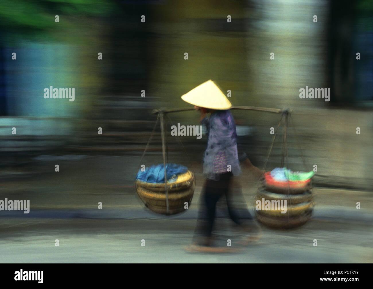 Persona con tradizionale hat trasporta carichi, Rush Hour in Vietnam, in Indocina Immagini Stock