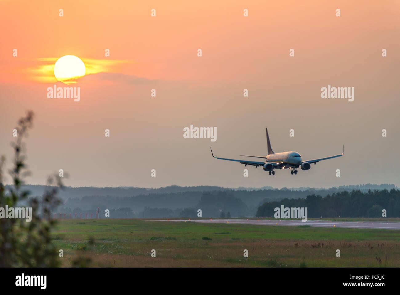 Un piano si avvicina all'aeroporto durante il tramonto. Immagini Stock