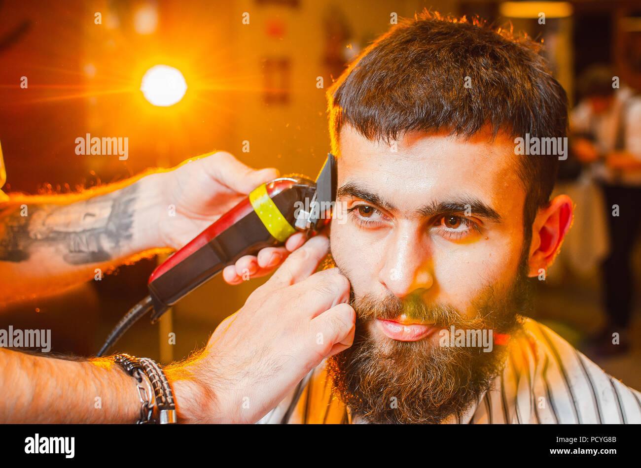 Barbiere fa un taglio di capelli sulla sua testa con un rifinitore per un  giovane ragazzo c14264fbee62
