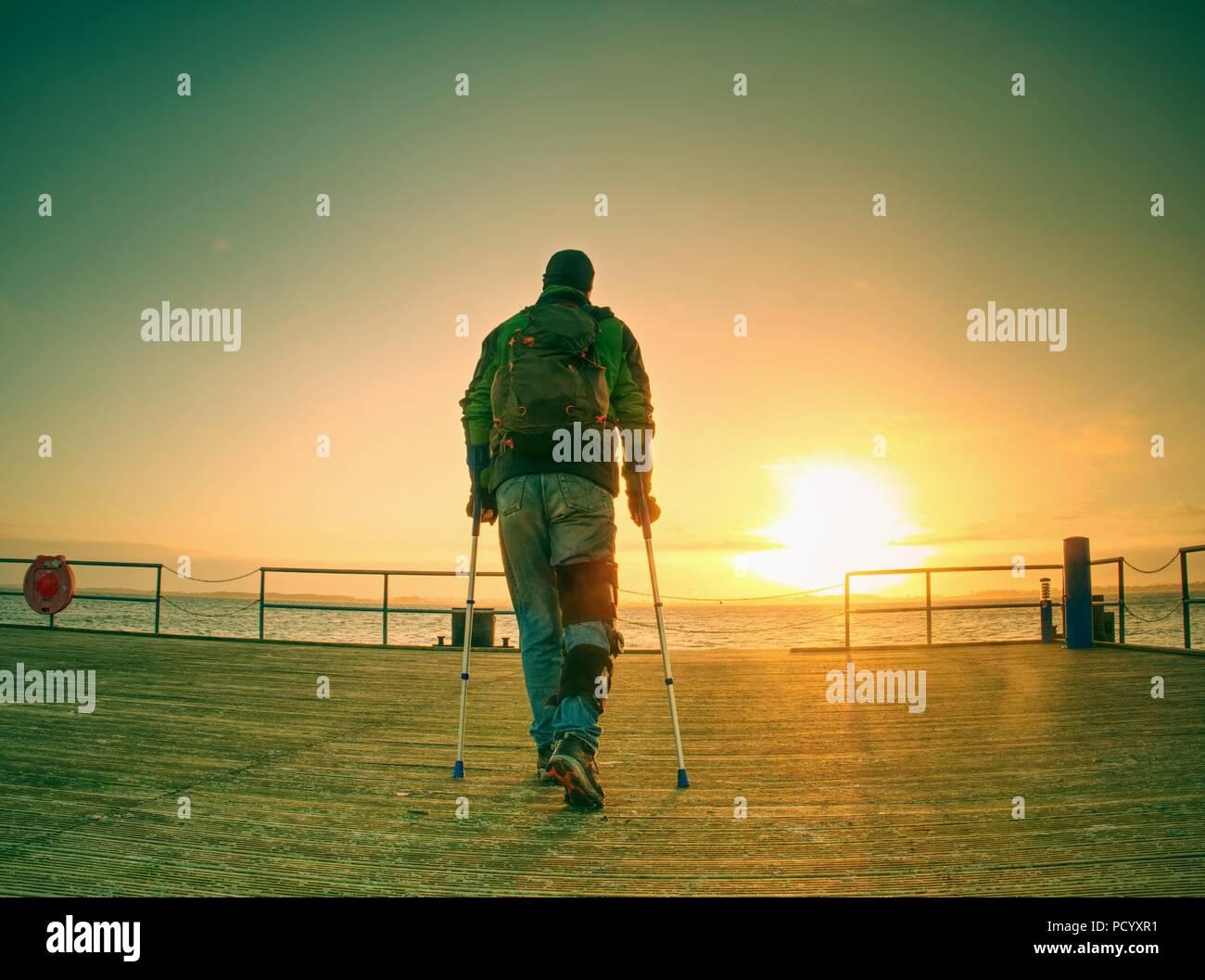Cupo nostalgico silhouette di sad lonely malinconico uomo adulto con giacca con cappuccio in piedi sul lago di Ponte entro la mattina presto e il pensiero Immagini Stock