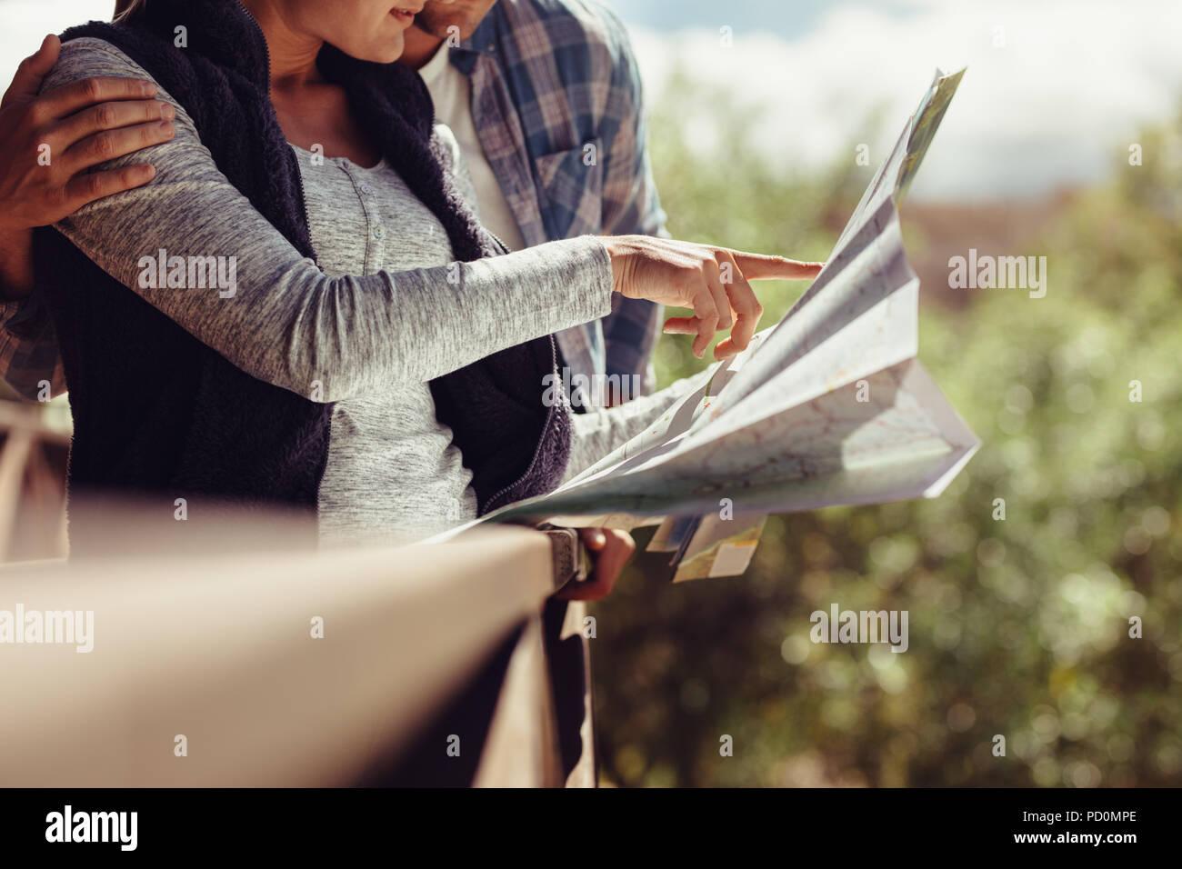Donna puntando verso la mappa permanente, mentre con il suo fidanzato. Coppia in cerca di destinazione di viaggio sulla mappa. Immagini Stock