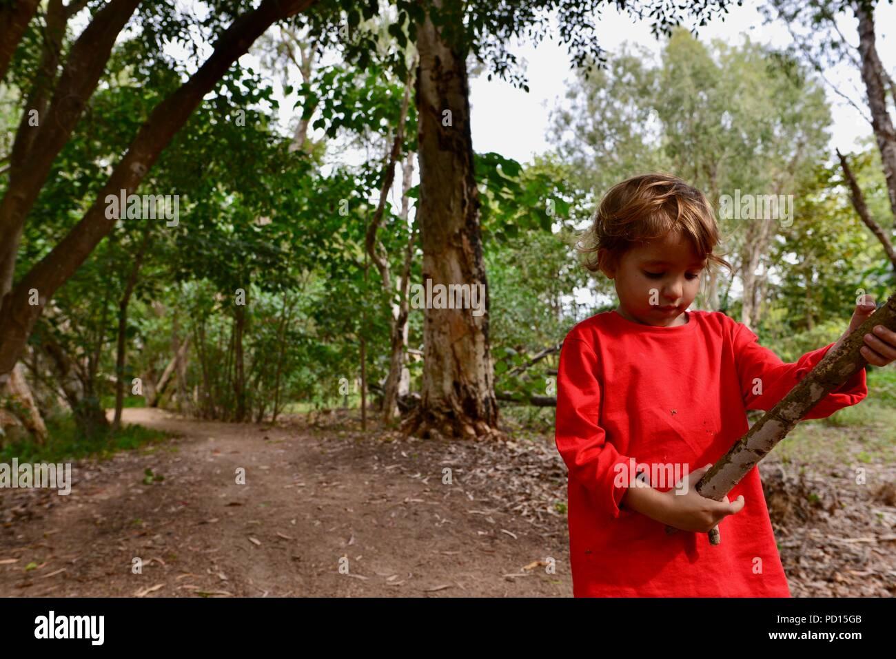 Bambino guarda un bastone ha appena prelevato, Booroona sentiero a piedi sul fiume Ross, Rasmussen QLD 4815, Australia Foto Stock