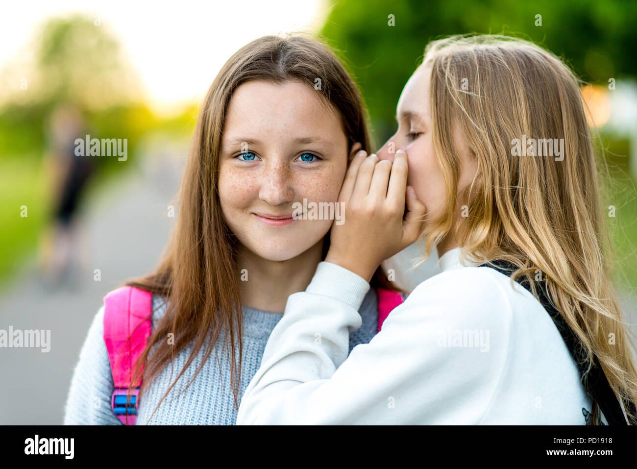 Due amiche schoolgirl. In estate in città. Racconta a un amico in orecchio, un segreto, davvero. Il concetto di sorpresa, migliori amici, regalo. L'emozione della felicità è il piacere di un sorriso. Immagini Stock