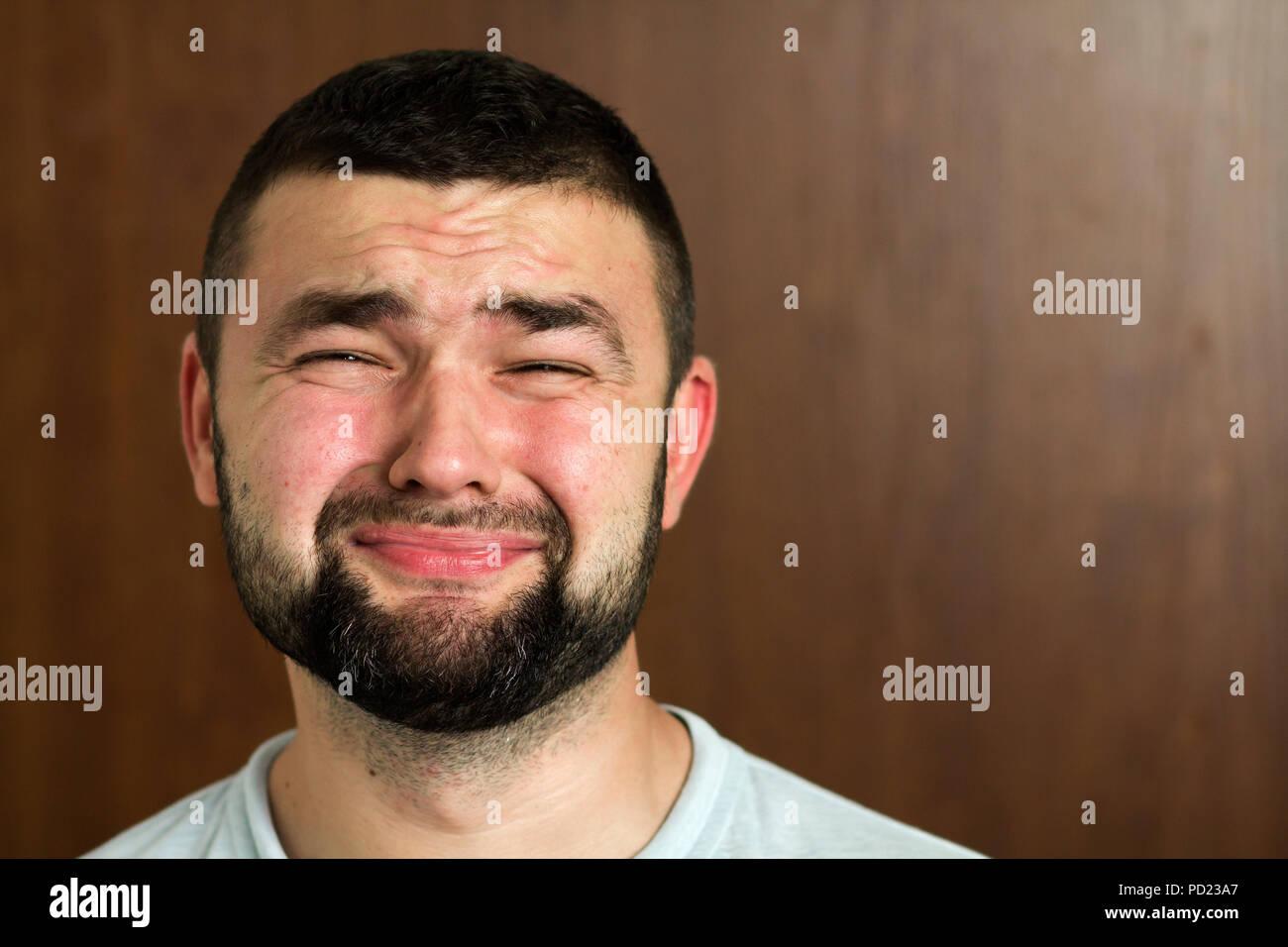Ritratto di bello barbuto dai capelli neri moderno intelligente giovane in  bicchieri con taglio di capelli corti e tipo occhi neri sorridente su sfondo  ... f184d566256d