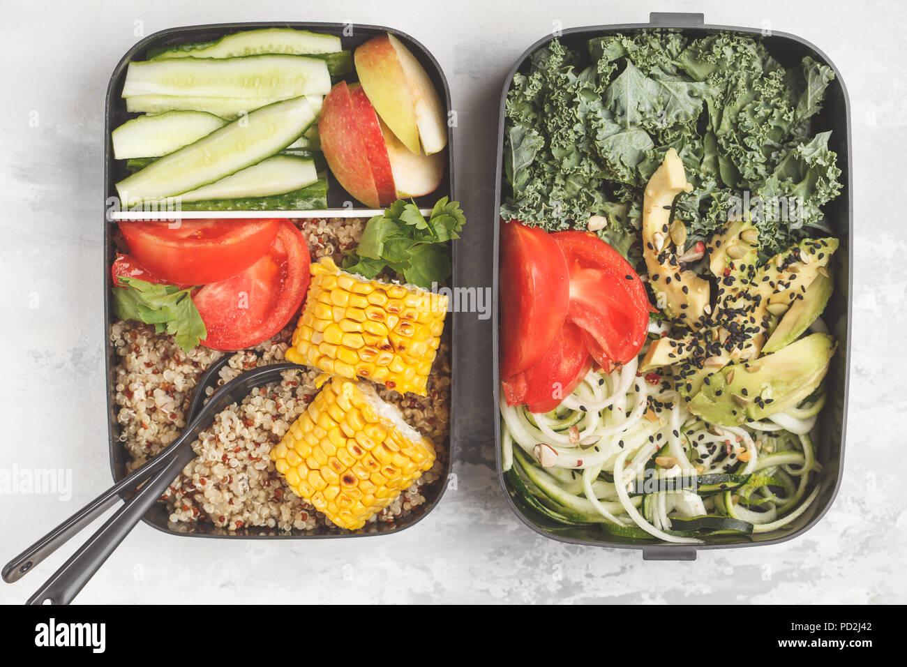 Pasto sano prep contenitori con la quinoa, avocado, mais, zucchine tagliatelle e Kale. Cibo da asporto. Sfondo bianco, vista dall'alto. Immagini Stock