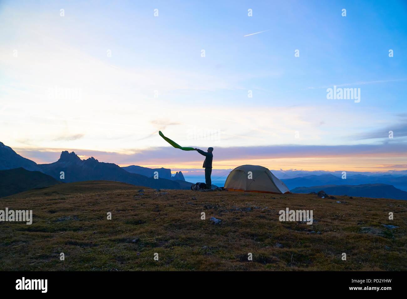 Escursionista preparazione al camp al tramonto, Canazei, Trentino-Alto Adige, Italia Immagini Stock