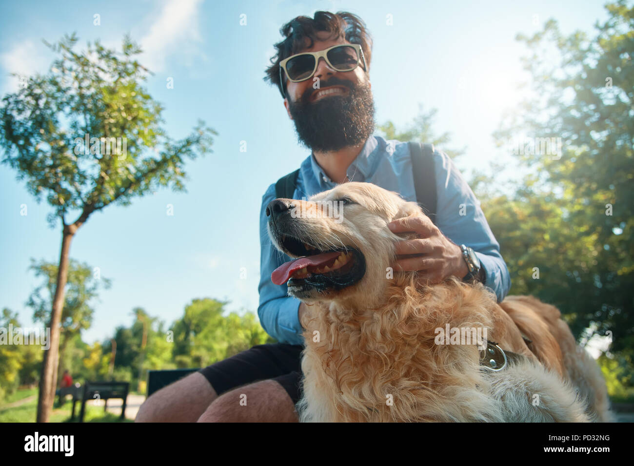 Uomo e cane divertendosi, giocando, facendo facce buffe mentre restin Immagini Stock