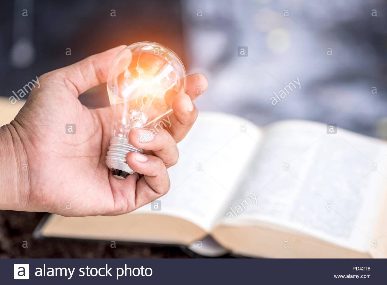 Creative designer azienda lampadine con il libro di testo e di sfondo per la nuova idea di innovazione Immagini Stock