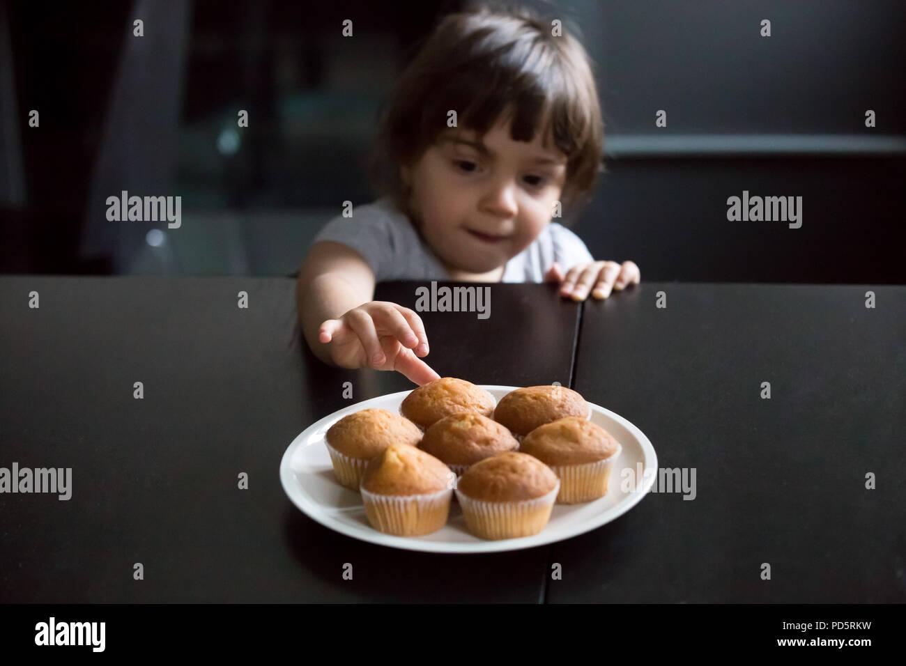 Carino ragazzina curiosa raggiungendo i muffin sul tavolo Immagini Stock