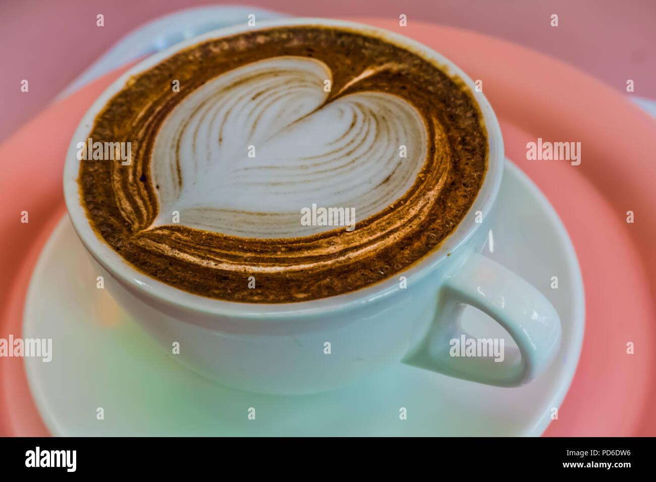 Tazza di caffè, cioccolato topping con cuore di colore bianco sulla parte superiore. Immagini Stock