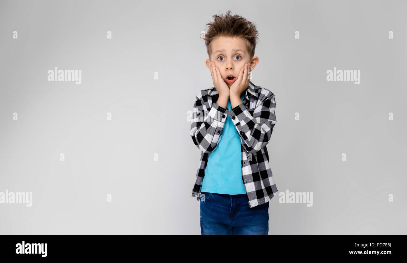 online store 6b2b1 9f45d Un bel ragazzo in un plaid shirt, camicia blu e jeans sorge ...
