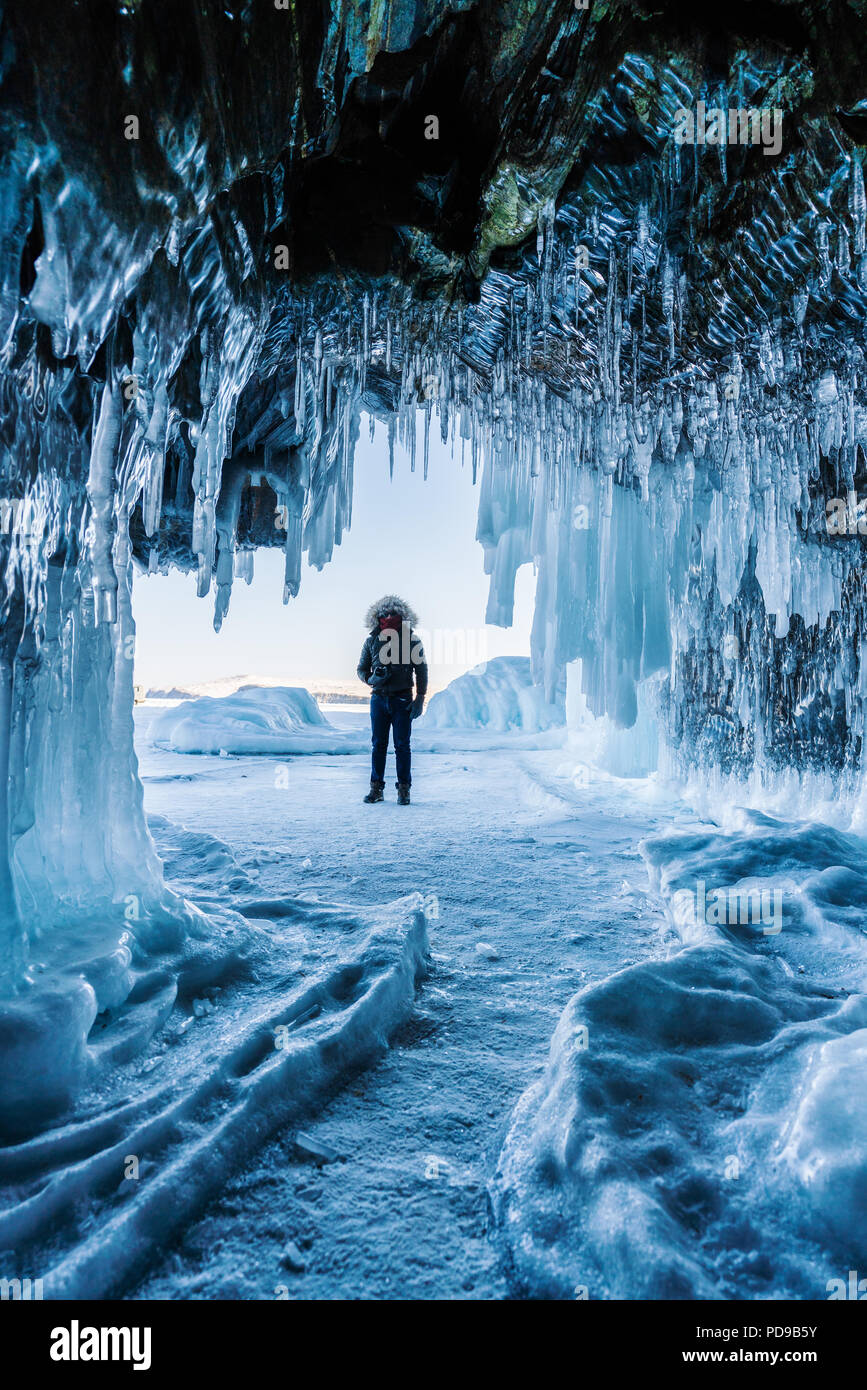 Viaggiare in inverno, un uomo in piedi sul lago ghiacciato Baikal con la grotta di ghiaccio di Irkutsk in Siberia, Russia Immagini Stock