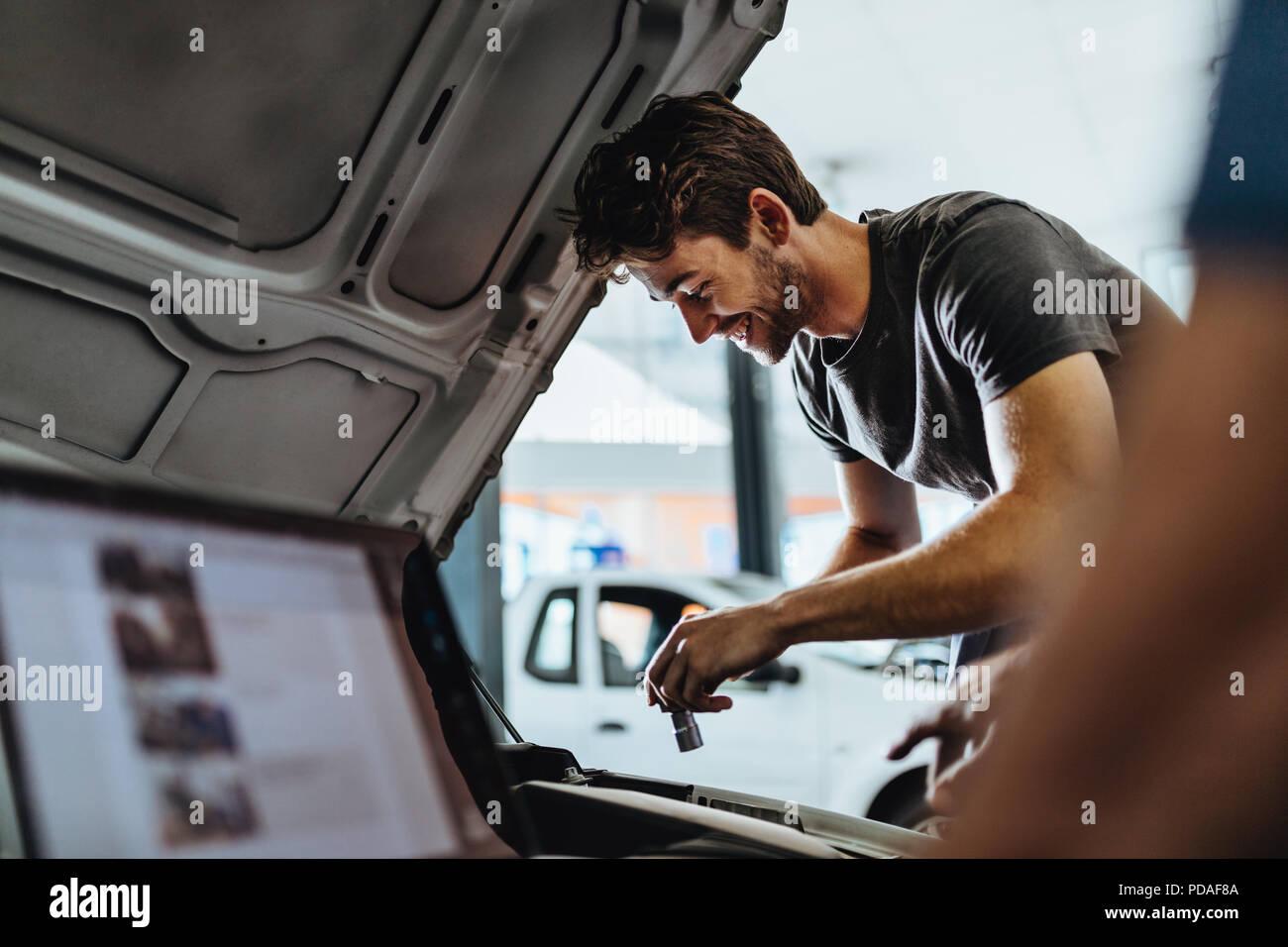 Sorridente giovane uomo che ripara la macchina in garage con un collega utilizzando laptop nella parte anteriore. Lavoro meccanico sotto il cofano di un veicolo. Immagini Stock