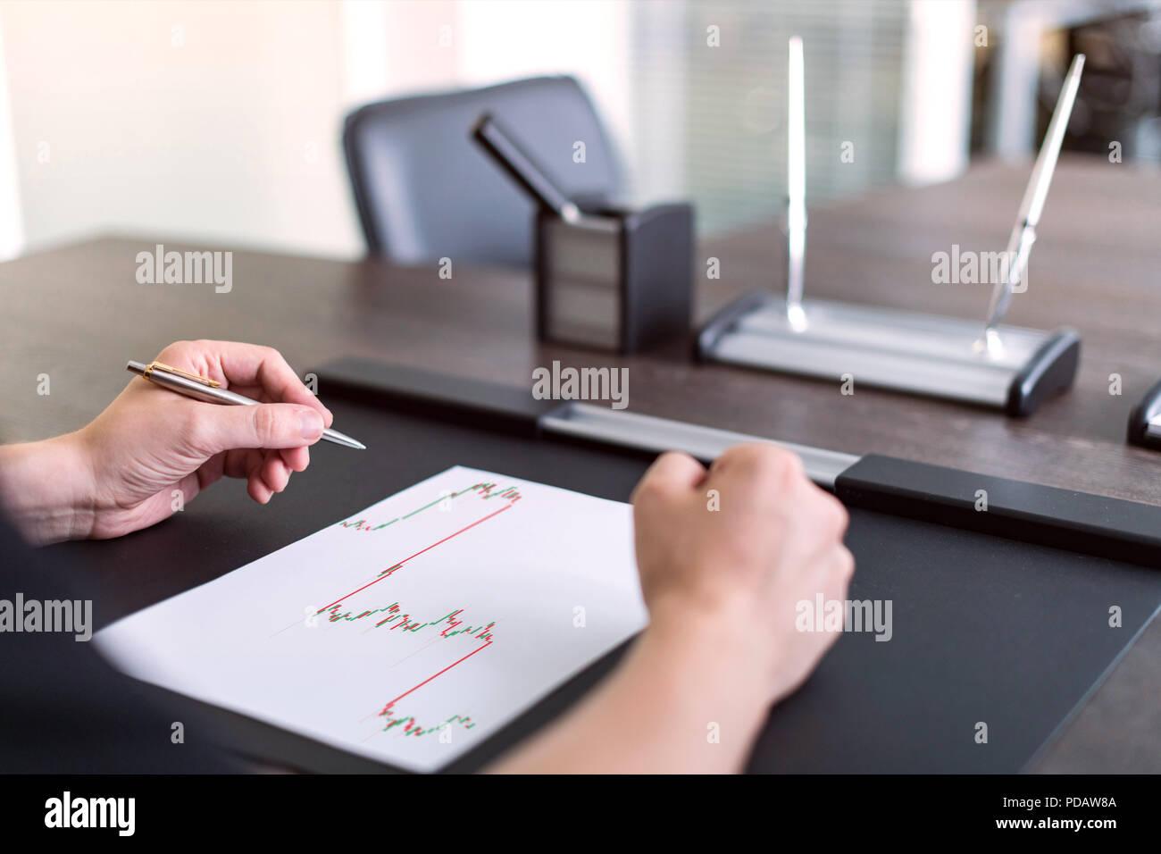 Uomo seduto a tavola e tiene la penna in mano sinistra. Ci sono fogli di carta con un diagramma di negoziazione sul tavolo. Concetto foto. Immagini Stock