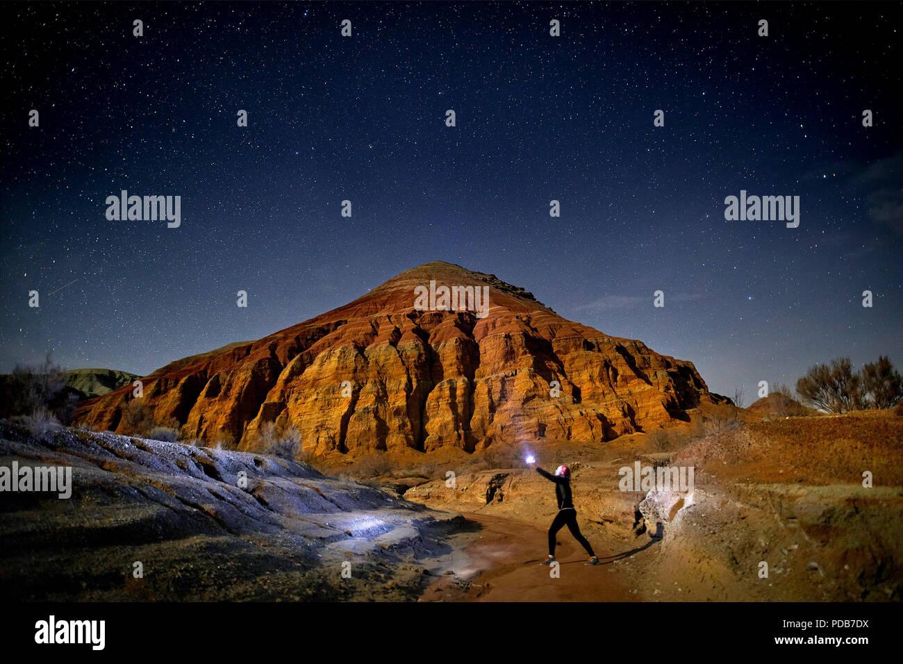 Uomo con testa luce nel deserto di notte sullo sfondo del cielo. Viaggi, avventuri e concetto di spedizione. Immagini Stock