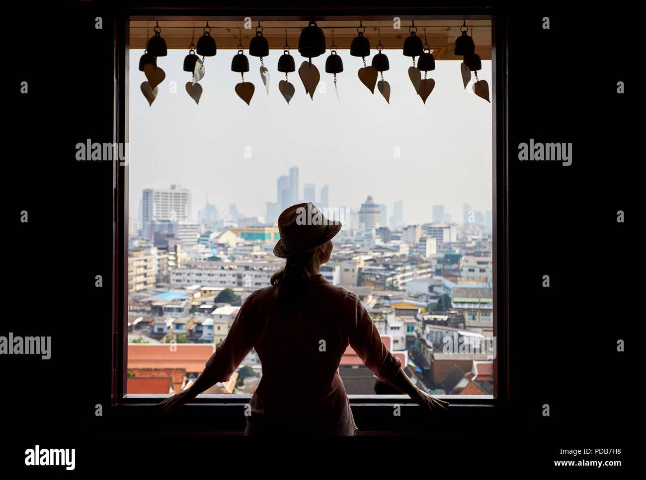 Silhouette di donna turistica cercando nella finestra per Bangkok City View grattacieli del quartiere degli affari da Golden Mountain Pagoda Wat Saket al coperto Foto Stock