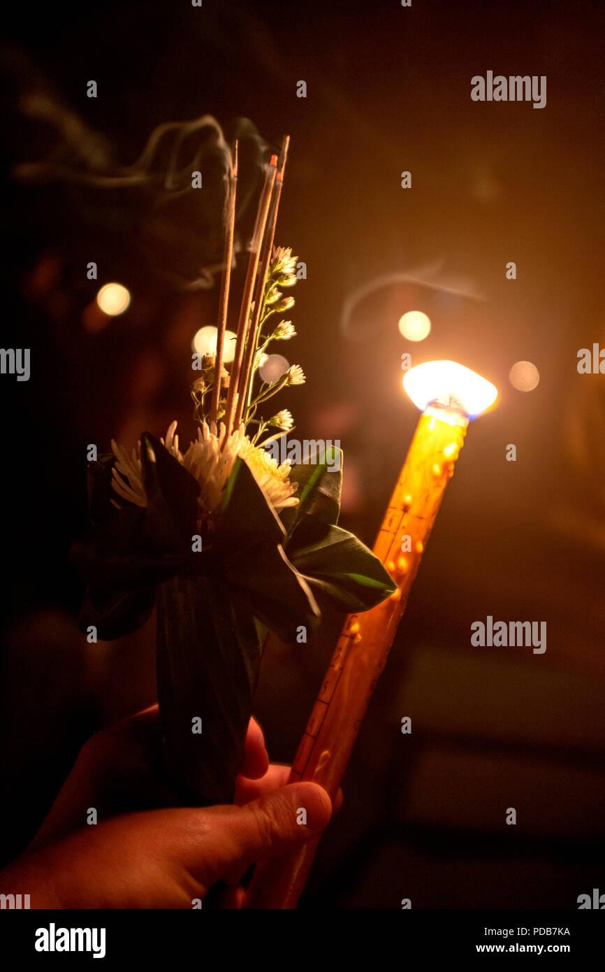 Mano azienda tailandese tradizionale offerta di incenso e fiori e candele Immagini Stock