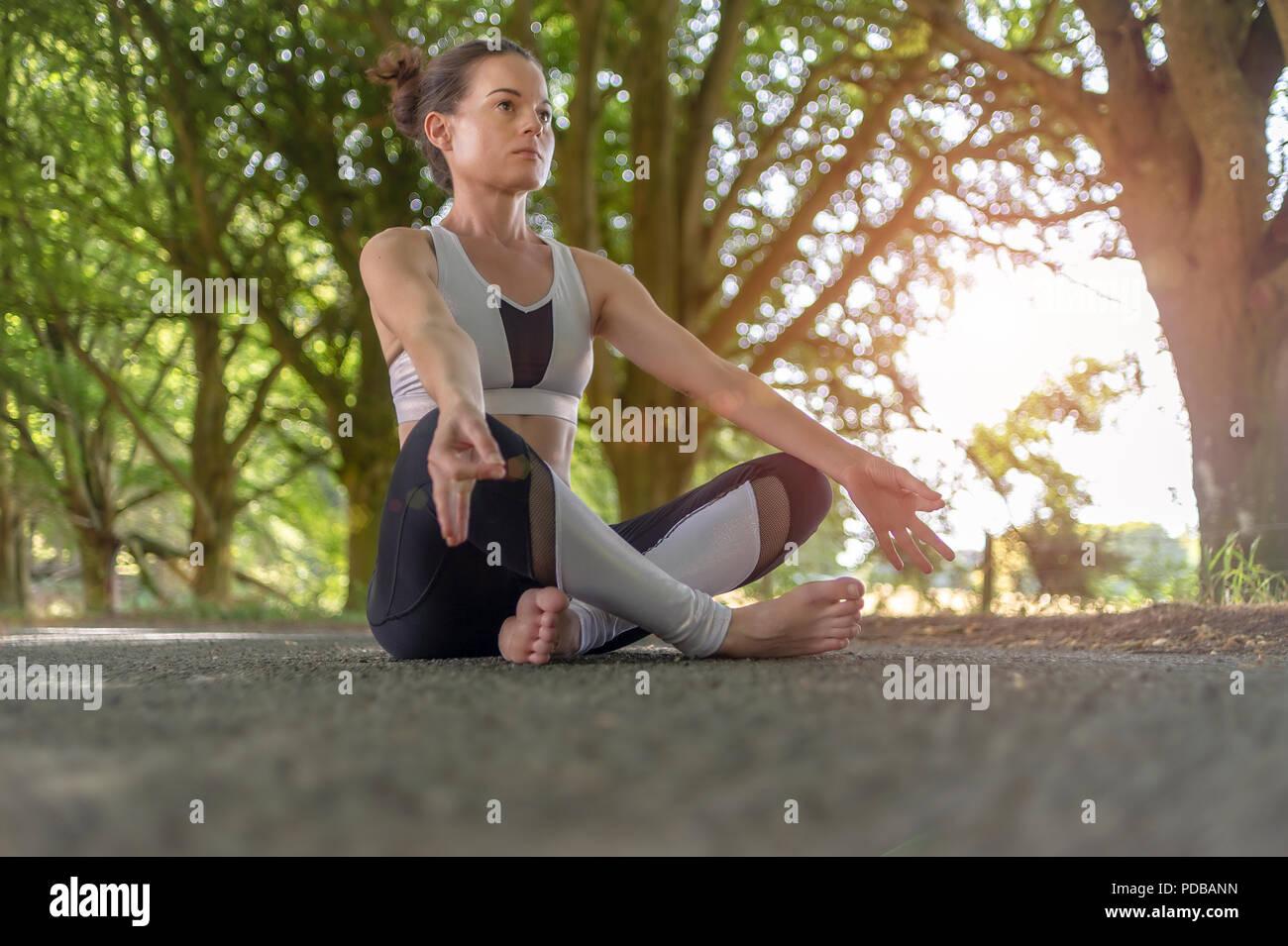 Donna seduta meditando esterno con alberi, Immagini Stock