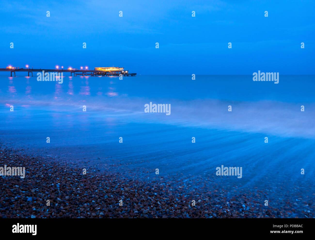 Onde che si infrangono lungo il lungomare di trattativa al tramonto con il Molo di trattativa illuminato in background. Immagini Stock