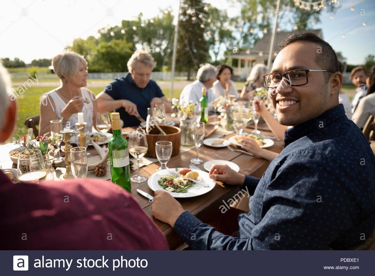 Ritratto uomo sorridente godendo soleggiato giardino partito il pranzo Immagini Stock