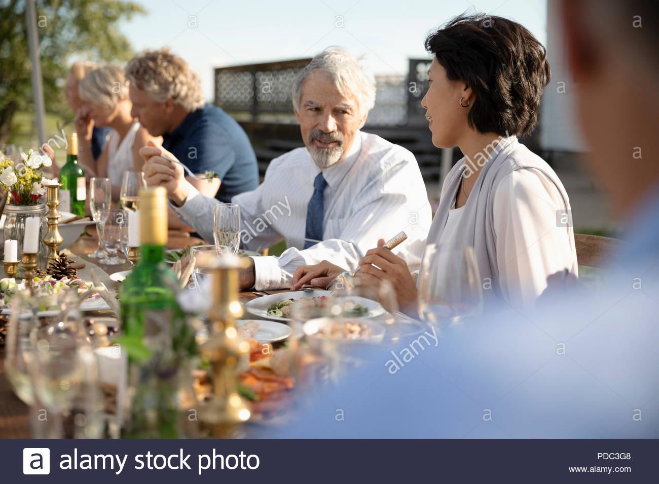 Paio di parlare e di mangiare al giardino soleggiato parte il pranzo Immagini Stock