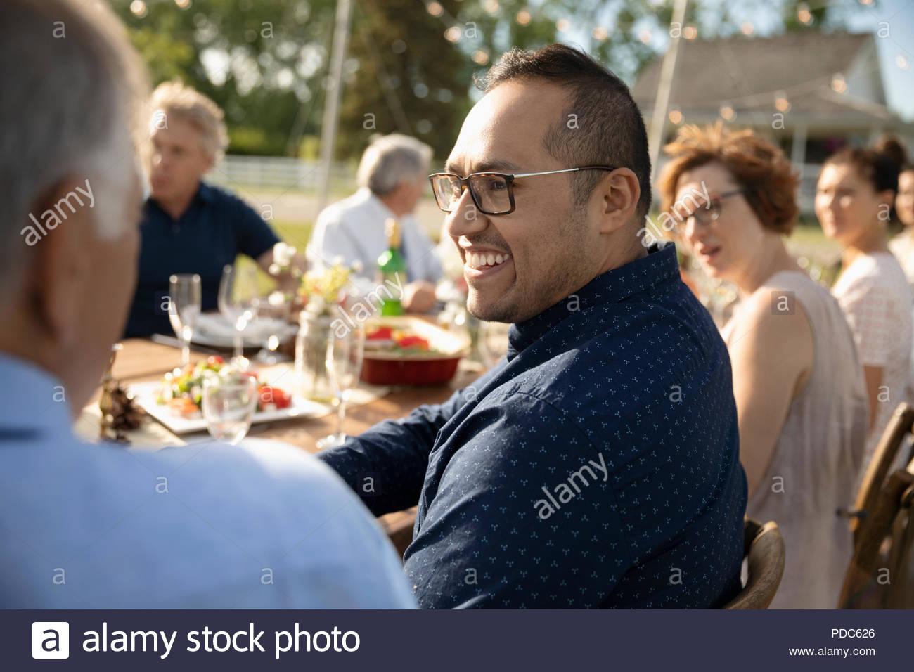 Uomo sorridente godendo di ricevimento di nozze il pranzo al patio tabella Immagini Stock