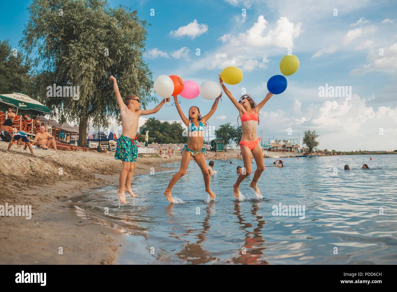 Dei bambini felici giocando con palloncini in mare. Bambini il divertimento all'aperto. La vacanza estiva e uno stile di vita sano concetto Immagini Stock