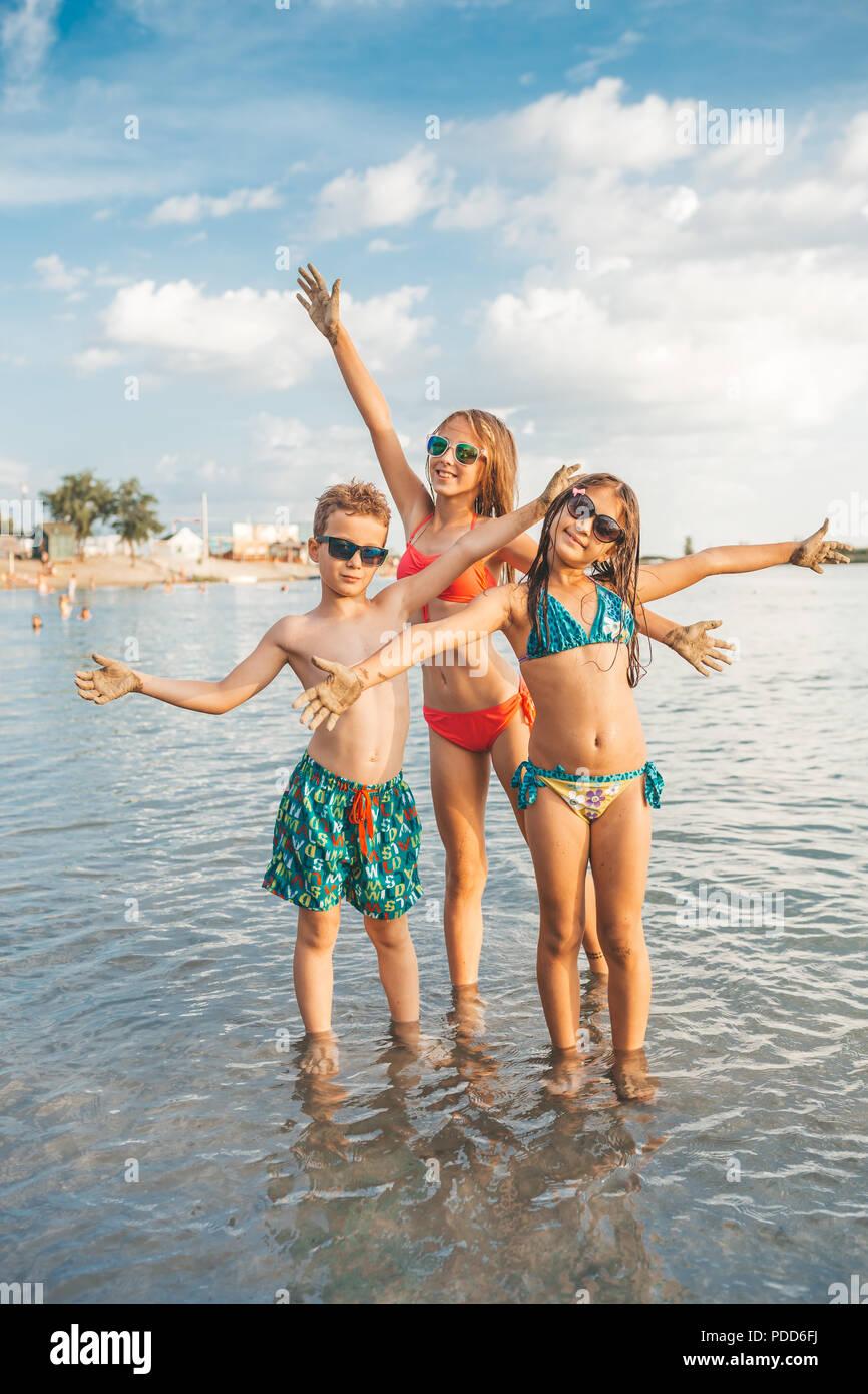 Dei bambini felici giocando in mare. Bambini il divertimento all'aperto e diffondere le loro mani e guardando la telecamera. Vacanze estive e lifest sani Immagini Stock